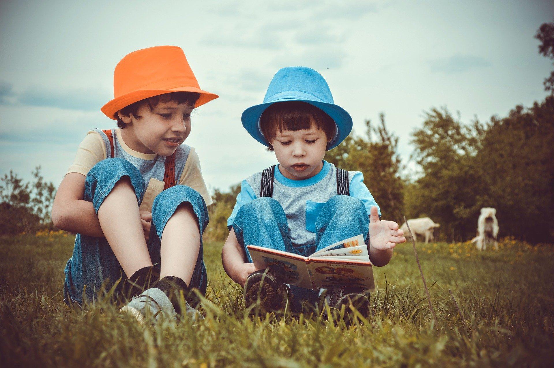 Kinder lesen auf einer Wiese